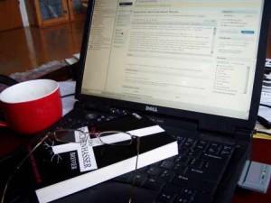 Das Kirchenhasser-Brevier und eine Brille auf einem Notebook. Daneben Kaffeetasse