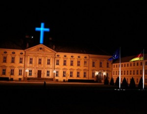 ein blaues Neonkreuz  ziert Schloss Bellevue, Montage: Ulli Schauen